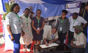 The County Assembly Speaker Hon. David Githanda signs the visitors' book at Senate's stand during the  Fourth Annual Legislative Summit in Kisumu. With him are Members of the County Assembly From left Hon. Caroline Muriithi, Hon.Rose Njeru,Hon. Joylisa Njagi,, Hon. Scolastica Nyawira, Hon. Kariuki Njiru and Hon. Gudson Muchina.