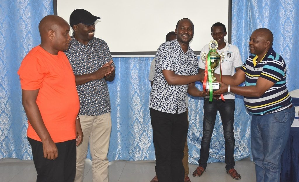 The County Assembly Dart's team present a trophy to the Members of the County Assembly Service Board.